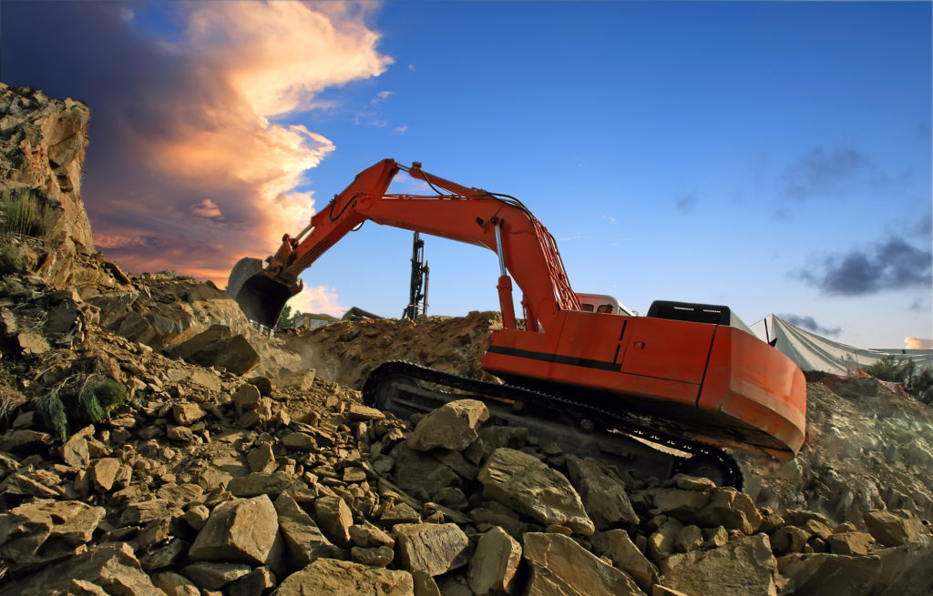 Excavator digging mountain by crushing rocks with its shovel